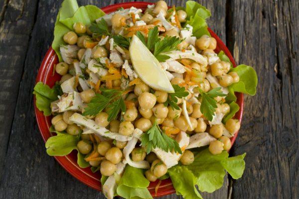 Салат с нутом и копчёной курицей на красной тарелке