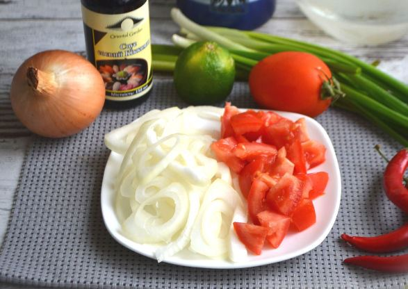 Нарезанный полукольцами репчатый лук и кубики помидора на тарелке