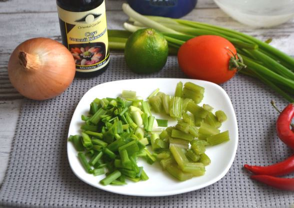 Измельчённый стебель сельдерея и зелёный лук на тарелке