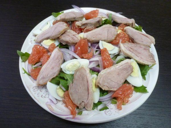 Салат с рукколой, красным луком, утиным мясом, перепелиными яйцами и грейпфрутом