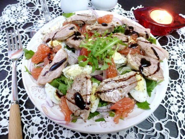 Салат с утиной грудкой и грейпфрутом на белой тарелке