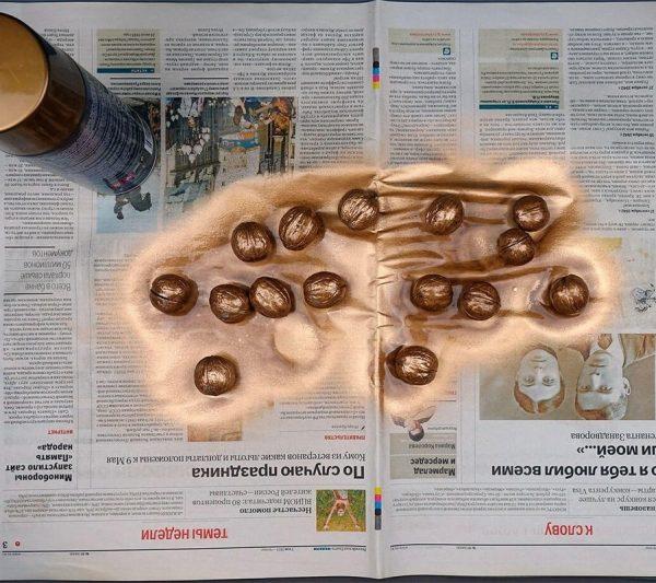 Окрашенные золотистой спреевой краской грецкие орехи на газете