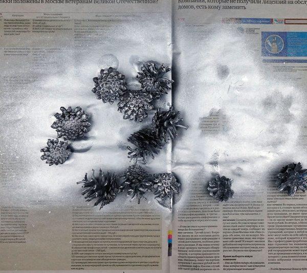 Шишки в серебристой краске на газете