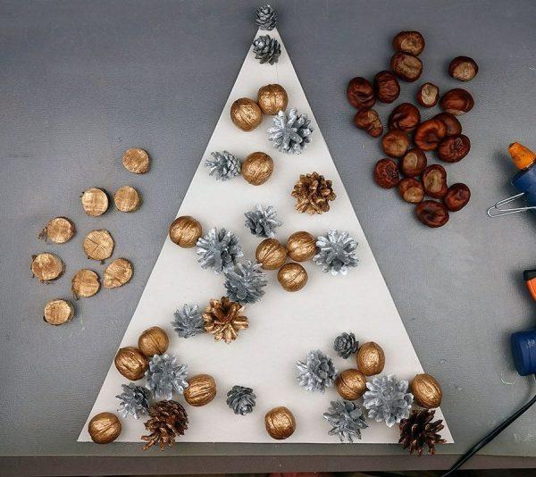 Окрашенные золотым и серебряным спреем шишки и грецкие орехи на картонной заготовке для ёлочки