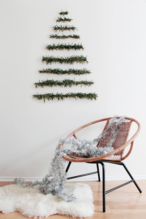 Самодельная ёлочка из деревянных планок и веточек свежего розмарина на стене, плетёный стул и пушистый белый коврик