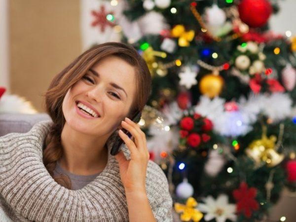 Девушка разговаривает по телефону на фоне ёлки