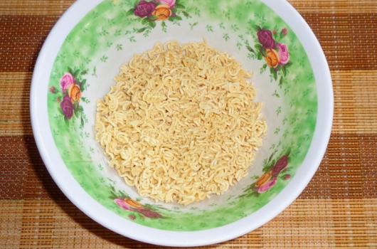 Ракрошенная на мелкие кусочки лапша быстрого приготовления в глубокой тарелке