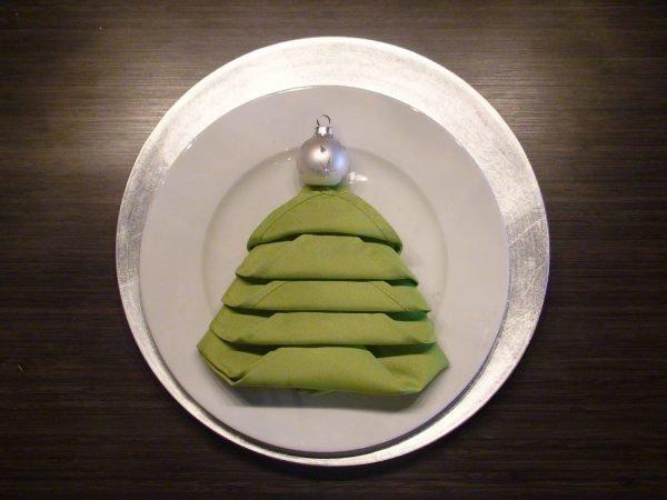 Салфетка, сложенная в виде ёлки, на тарелке