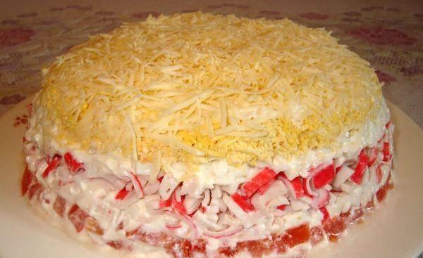 Слоёный салат с крабовыми палочками, помидорами и твёрдым сыром на тарелке