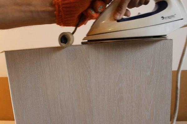 Наклеивание экошпона на дверь с помощью валика и утюга
