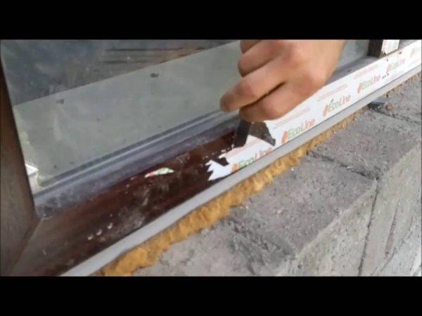 Рабочий снимает плёнку ножом
