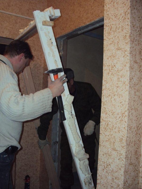 Рабочий снимает дверную коробку