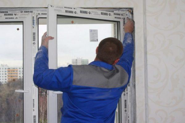 Рабочий меняет пластиковую дверь