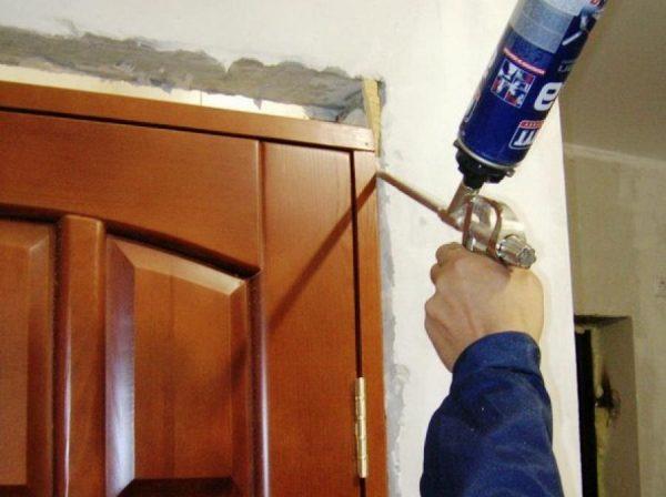 Рабочий уплотняет зазор между дверной коробкой и стеной