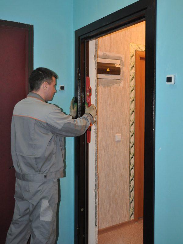 Рабочий выравнивает дверь