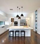 Группа из чёрных подвесных светильников на белой кухне