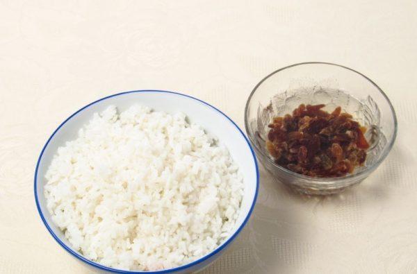 Отварной рис и распаренный изюм в мисочках на столе