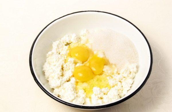Творог, сырые яйца и сахарный песок в миске
