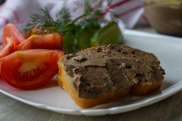 Хлеб с паштетом из куриной печени, свежие овощи и зелень на тарелке
