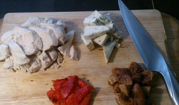 Порезанные на кусочки продукты для куриного паштета на разделочной доске с ножом
