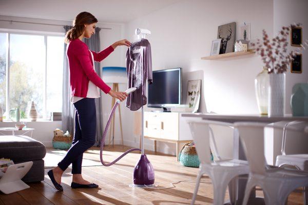 Женщина пользуется отпаривателем для одежды