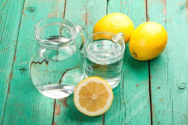 Графин и стакан с водой в окружении лимонов