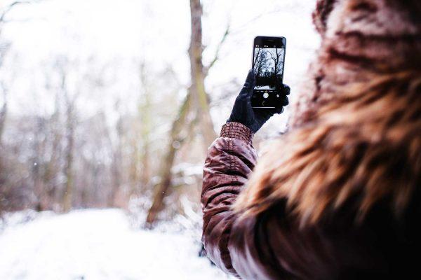 Девушка фотографирует зимнюю улицу