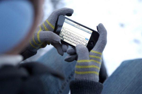 Парень печатает сообщение в специальных перчатках для смартфонов
