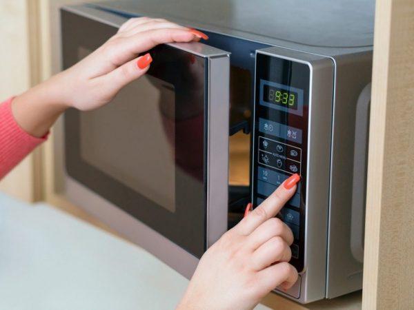 Женщина выбирает программу для приготовления в микроволновке