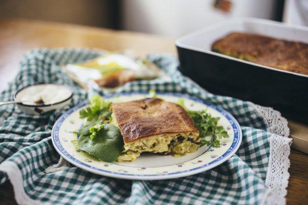 Кусочек заливного пирога с капустой на тарелке с зеленью