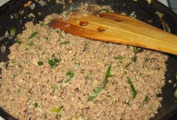 Обжаренный мясной фарш с луком в сковороде и деревянная лопаточка