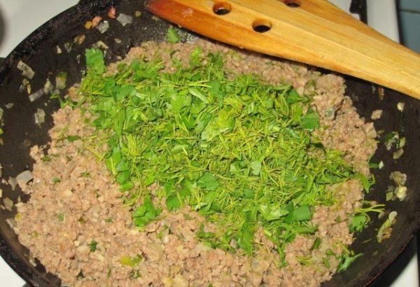 Обжаренный мясной фарш и мелко нарубленная свежая зелень в сковороде