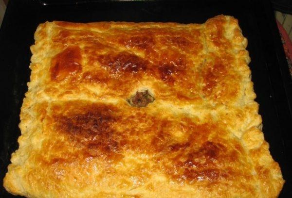 Готовый пирог с мясом из слоёного теста на противне