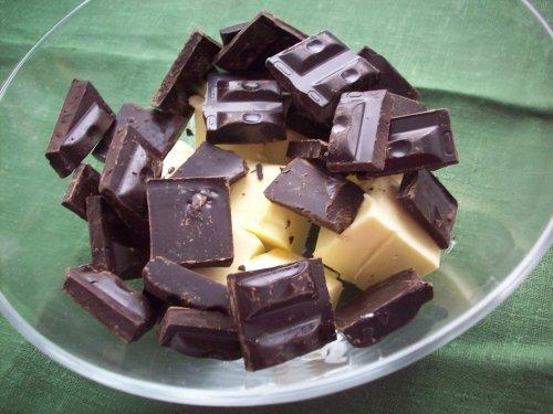 Кусочки сливочного масла и чёрного шоколада в стеклянной миске