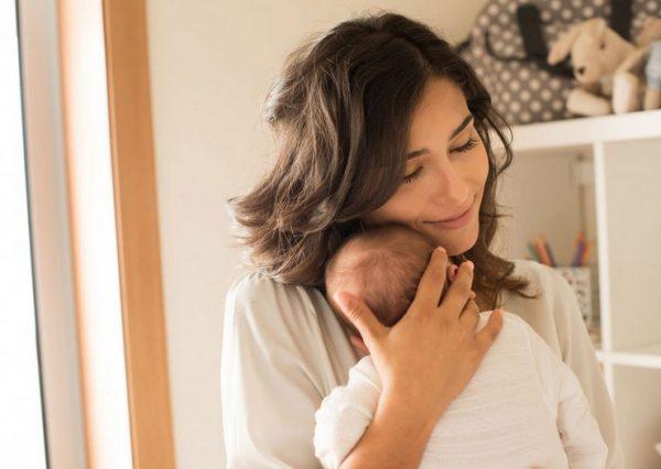 Мать держит икающего грудничка на руках