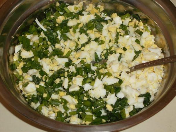 Измельчённые варёные яйца и зелёный лук в миске