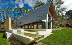 Современный загородный дом с фальцевой крышей, которая переходит в фасад. Материал кровельного покрытия титан-цинк NedZink.