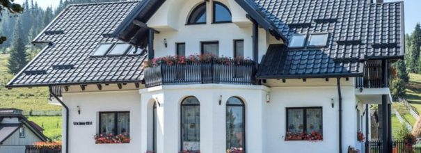 Красивый загородный дом с кровлей из металлочерепицы.