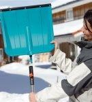 Девушка со снегоуборочной пластиковой лопатой