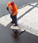 Рабочий заливает крышу битумом