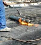 Рабочий делает гидроизоляцию наплавляемым материалом