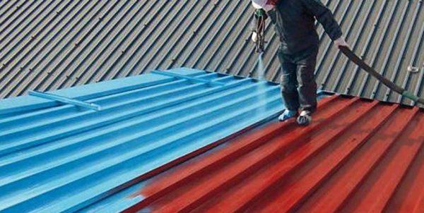 Рабочий наносит окрасочную гидроизоляцию на крышу