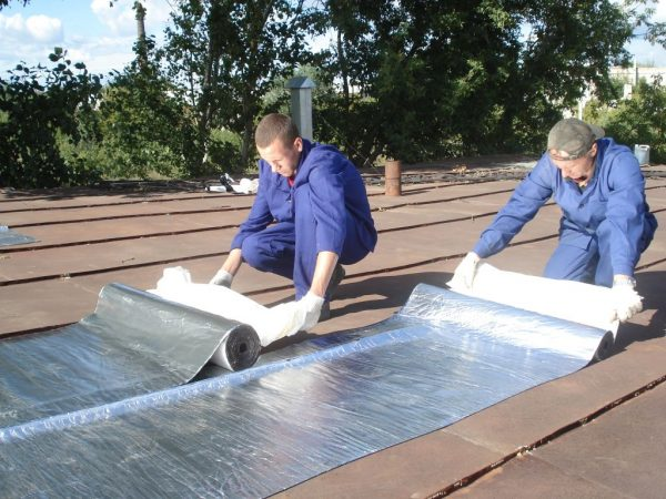 Рабочие укладывают листовые полотна на крышу