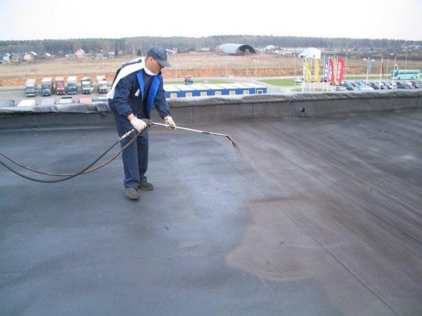Рабочий напыляет гидроизоляцию на бетонную крышу