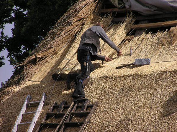 Рабочий на стремянке укладывает солому