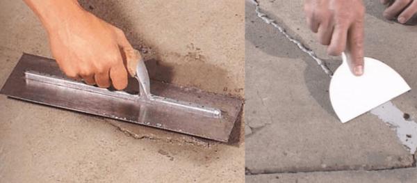 Рабочий заделывает трещины в бетонной стяжке