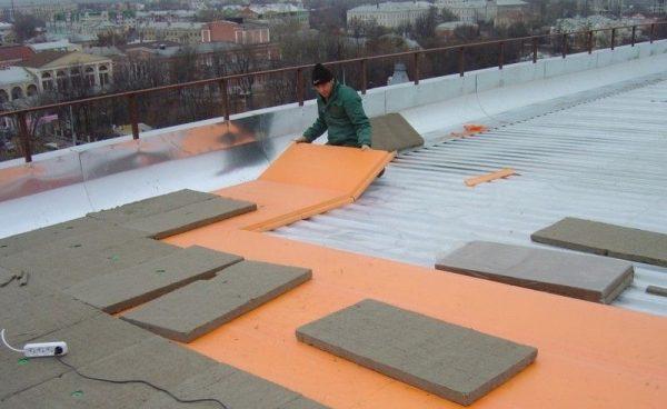 Рабочий укладывает теплоизоляционные маты