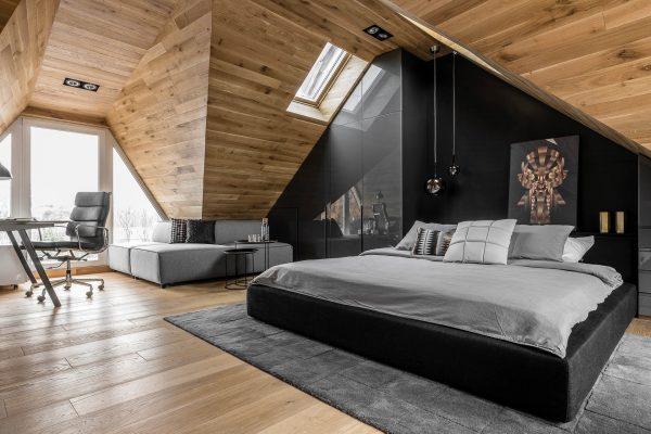 Спальня с большими окнами и тёмными деревянными панелями на стенах