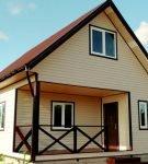 Дом с мансардой, покрытый сайдингом