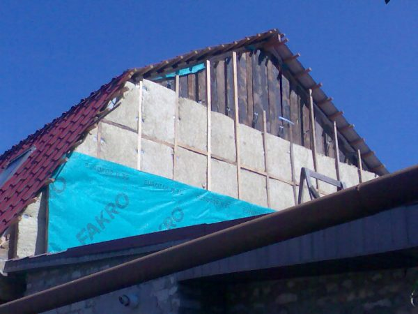 Процесс укладки утеплителя на фронтон